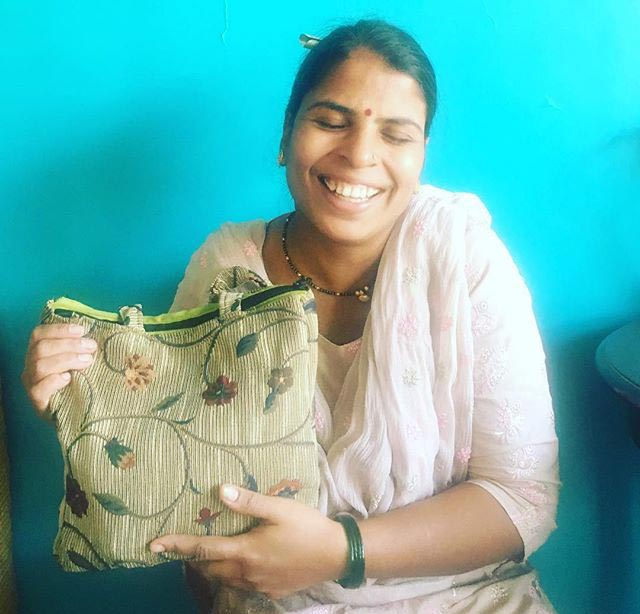 A village woman showing off the bag made by her with recycled cloth.